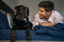 Young Man Looking At His Pet Dog Sitting Beside On Bed.