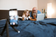Cheerful Man And Pretty Daughter Bloggers With Laptop Wave Hands To Greet Followers At Home