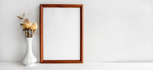 A Wooden Empty Photo Frame On A White Table And Flowers In A Vase. A Fashionable Wedding Or Holiday Banner.