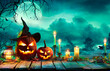 Leinwandbild Motiv Halloween At Night - Pumpkins With Witch Hat And Candles On Table In Mystery Landscape