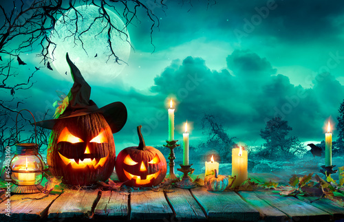 Halloween At Night - Pumpkins With Witch Hat And Candles On Table In Mystery Landscape