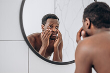 Young African-American Man With Bare Torso Reflection Looking In Round Mirror Making Face In Spacious Bathroom Close Backside View