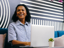Woman Using Laptop In Office Lounge Area