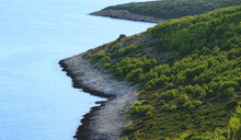 Rocky And Inaccessible Sea Coast With Green Mediterranean Vegetation On The Coast Near The Blue Sea