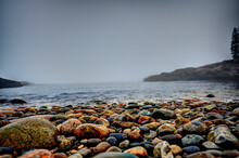 Multi-colored Round Rocks On Little Hunters Beach In Acadia National Park, Maine. Tide Coming In As Waves Crash.