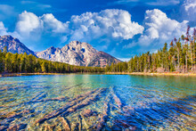 Shot Of The Mountains And Their Reflection In The Lake In The Background Of A Blue Cloudy Sky.