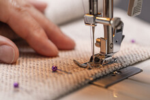Sewing Machine Foot On Fabric With Needle And Thread Ready Forwork. Operator's Hand On The Material, Close-up.