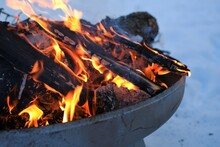 Bonfire.Burning Firewood In The Winter Snow Garden.Burning Firewood Background.Flames And Sparks