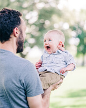 Happy Baby Boy Laughing As Dad Lifts Him In Air At Park In Summertime