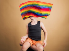 Unrecognizable Boy With LGBTQ Flag On Beige Background