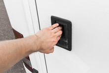A Man's Hand Opens Or Closes The Luggage Compartment Of A Vehicle, Car Or Bus By The Door Handle