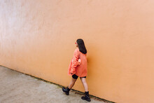 Young Woman Walking Near Orange Wall