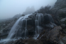 Cascades With Fast Water Flows In Mountains On Foggy Day