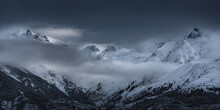 Landscape Of Snowy Mountains Covered By Clouds
