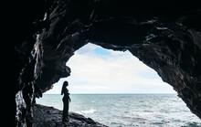 Anonymous Traveler Admiring Wavy Sea Against Cave