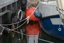 Orange Buoy With Reflection In The Water And Detail Of A Fishing Boat Tied At The Dock In The Port, Copy Space, Selected Focus,