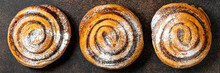 A Sweet Spiral Bun With Poppy Seeds And Powdered Sugar Of A Large Size On A Dark Background. Delicious Yeast Pastries Top View. The Concept Of Home-made High-calorie Baking. Banner