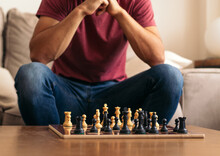 Crop Thoughtful Player On Sofa Against Chess Board In House