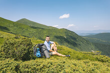 Mountain Hiking Concept. A Guy With A Big Backpack Squatting To Rest. Hiker On Top Of A Mountain