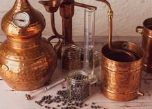 Alambique De Cobre Utilizado Para Destilar Con Botánicos, Enebro, Cardamomo Y Accesorios Sobre Una Mesa De Madera.