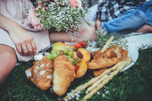 Family Picnic In The Woods With Croissants, Fruit And Brie Cheese Decorated With Wildflowers On Pine Branches And Cones, Side View Close-up