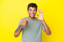 Young Handsome Brazilian Man Isolated On Yellow Background Showing Ok Sign And Thumb Up Gesture
