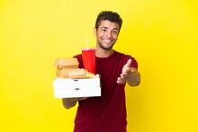 Young Brazilian Man Holding Pizzas And Burgers Isolated Background Shaking Hands For Closing A Good Deal