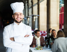 Portrait Of Professional Chef On Background With Restaurant Guests