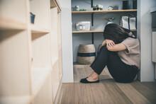 暗い部屋で女性が一人床に座って膝を抱えている woman Room