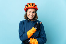Young Cyclist Woman Isolated On Blue Background Pointing To The Side To Present A Product
