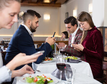 Modern Young People Busying With Phone During Evening Meal At Restaurant