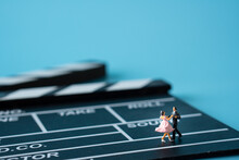 Miniature Of Man In Suit And Woman In Pink Dress Dancing On Clapperboard.