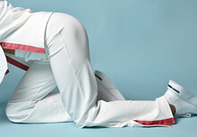 Closeup Of Woman Legs Standing On All Fours, Wearing White Trendy Pantsuit With Pullover, Sweater, Kimono Style And Fashionable Sneakers