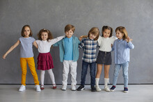 Cheerful Little Friends Gathered All Together. Studio Group Portrait Of Six Happy Young Kids. Team Of Adorable Children In Casual Wear Standing Near Grey Wall, Hugging, Smiling And Looking At Camera