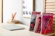 Leinwandbild Motiv Modern workplace with magazines near light wall