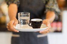 Cropped Image Of Black Coffee Mug With A Glass Of Water On Serving Tray Hold By Female Barista