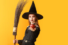 Young Witch With Apple On Color Background