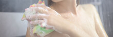 Young Smiling Woman Washing Herself With Washcloth In Shower