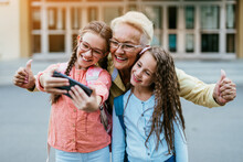 Happy Grandmother Came To Pick Up Her Grandchildren At School. They Are Taking Selfie Together.