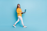 Full length profile side photo of young business woman happy positive smile go step meeting laptop isolated over blue color background