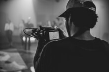 Grayscale Shot Of Cameraman Holding Camera On A Studio