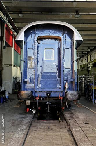 Fototapeta Vertical shot of a blue train wagon parking in metal rod in workshop
