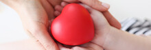 Little Girl And Mother Hands Holding Red Toy Heart Closeup