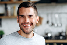 Portrait View Of The Handsome Man Sitting At The Table And Smiling While Looking At The Camera. Male Person At The Kitchen Stock Photo