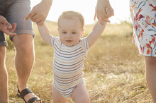 Cute Toddler Holding Hands His Parents And Training To Walk On Field At Sunset