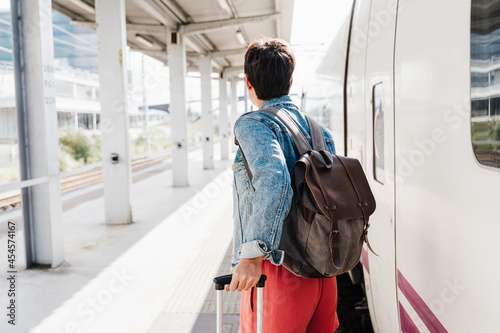 Fotografie, Obraz close up of backpacker caucasian woman holding luggage at train station ready to catch the train