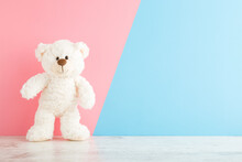 Smiling White Teddy Bear Standing On Wooden Floor At Light Pink Blue Wall Background. Pastel Color. Empty Place For Inspiration, Emotional, Sentimental Text, Quote Or Sayings. Closeup. Front View.