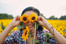 Portrait Of A Young Woman In A Shirt In The Sunflower Field Hold Eyes With Sunflowers