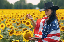 Young Woman Farmer With American Flag And Tablet PC In The Sunflower Field.