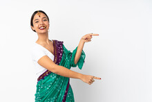 Young Indian Woman Isolated On White Background Pointing Finger To The Side And Presenting A Product